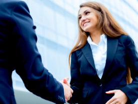 smiling young entrepreneur and business owner shaking hands