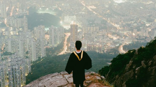 person in graduation robes standing on cliff over looking buildings