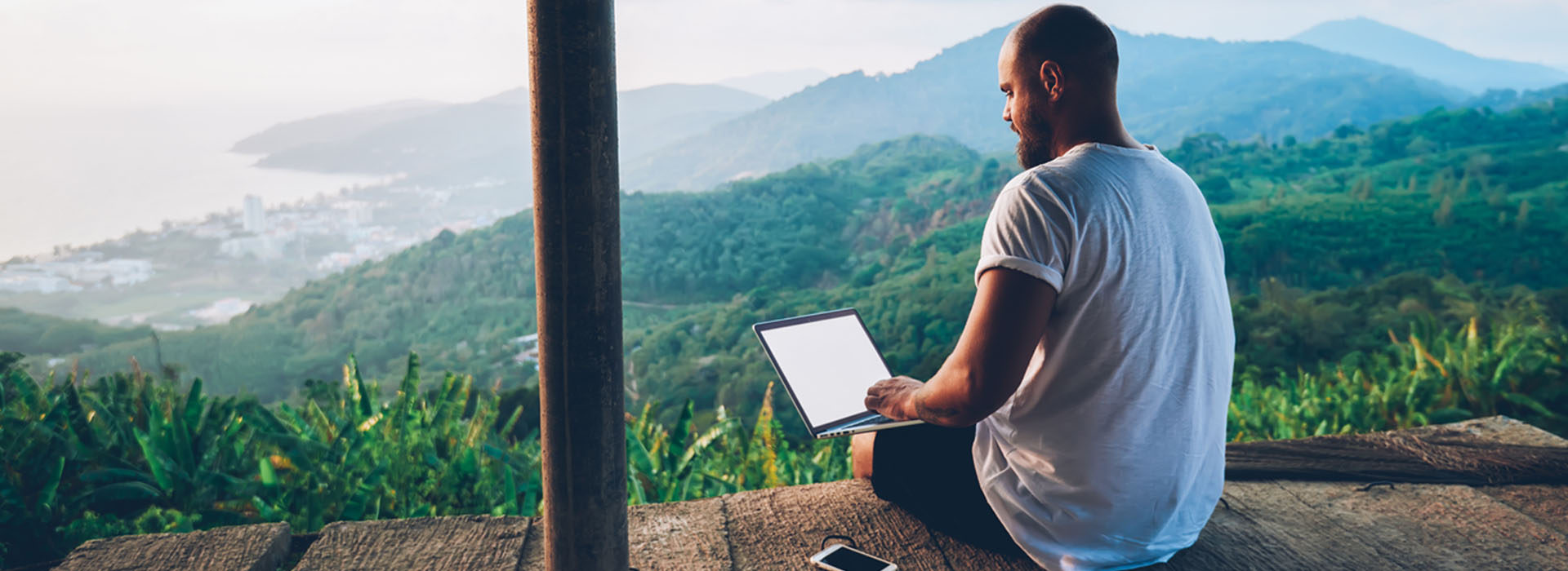 male freelancer on laptop with forest view