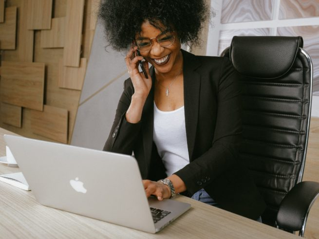 happy business owner on phone with laptop