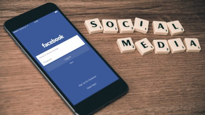 phone showing Facebook next to letters spelling social media